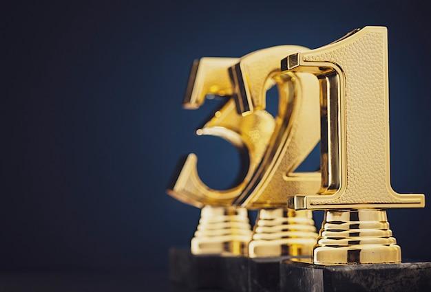 Tres trofeos dorados delante de azul
