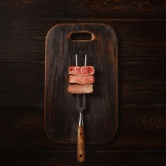 Tres trozos de carne en un tenedor para carne. tres tipos de asado de carne, raro, mediano, bien hecho.