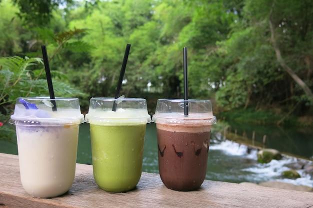 Tres vasos de bebida: cacao helado, té verde y jugo de coco frappe colocado sobre la mesa de madera en un ambiente de naturaleza fresca rodeado de árboles y un pequeño arroyo