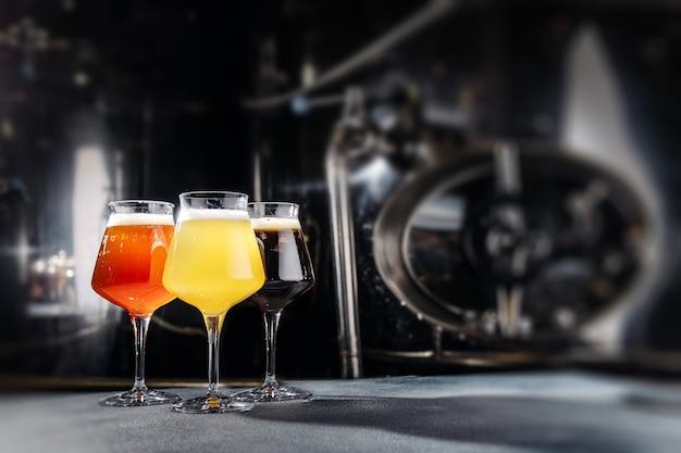 Tres vasos de cerveza en el fondo oscuro.