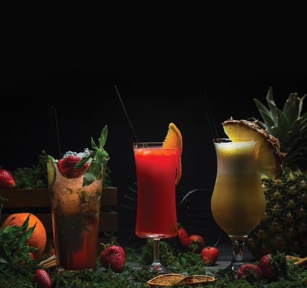 Tres vasos de cócteles de frutas tropicales.