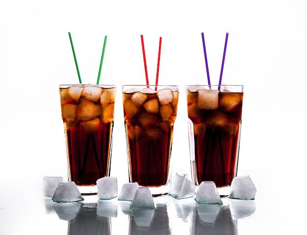 Tres vasos de cola con hielo y pajitas sobre un fondo blanco.
