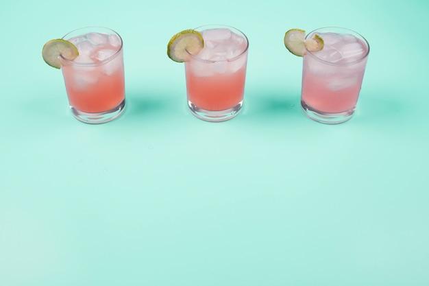Tres vasos de jugo de toronja con rodajas de limón y cubitos de hielo sobre el fondo de menta