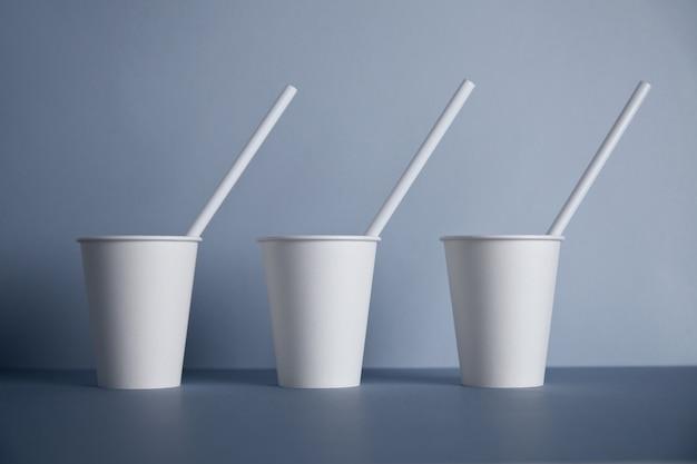 Tres vasos de papel blanco para llevar sin tapas con pajitas en el interior presentados en el centro