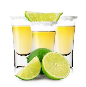 Tres vasos de tequila dorado con lima entera y en rodajas