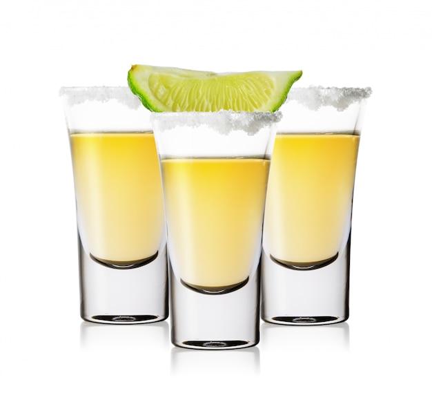 Tres vasos de tequila dorado con sal y lima