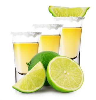 Tres vasos de tequila dorado con soporte de lima entera y en rodajas