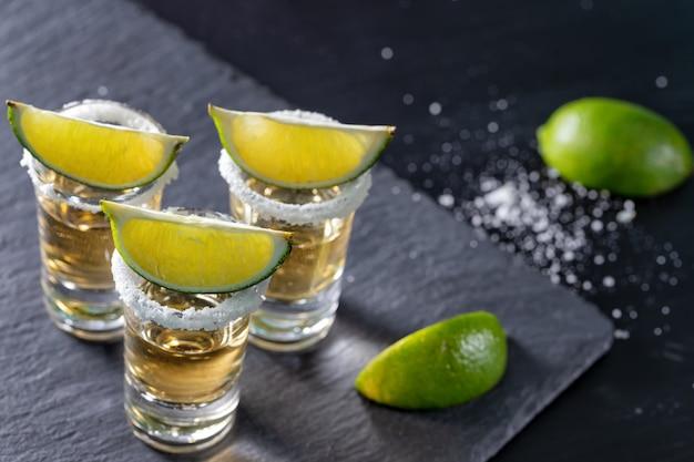 Tres vasos de tequila mexicano y lima