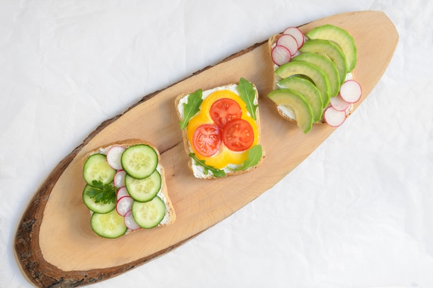 Tres vegetariano o vegano sandwich sobre una tabla para cortar sobre un fondo blanco.