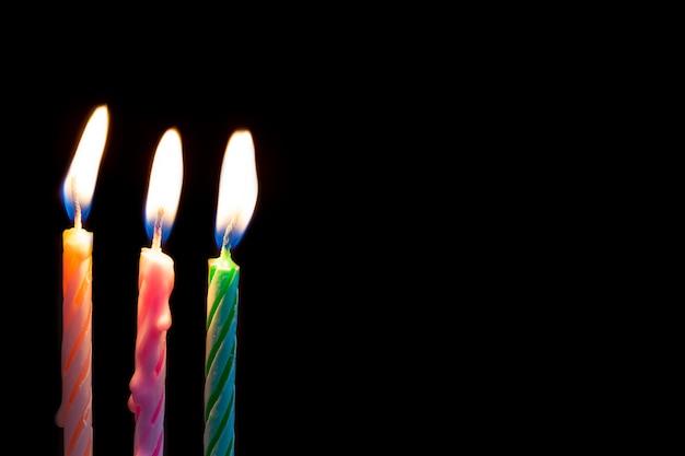 Tres velas de cumpleaños sobre fondo negro