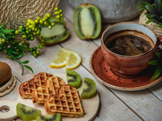 Tres waffles en forma de corazón con frutas y una taza de espresso