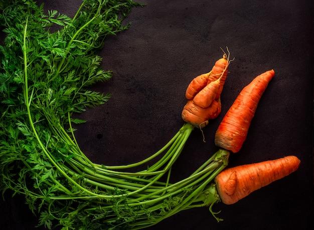 Tres zanahorias de cosecha propia con cáscaras, incluidas algunas feas