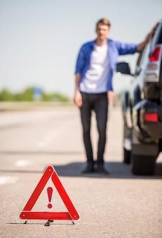 Triángulo rojo de advertencia con un coche averiado en la carretera.