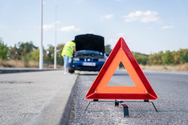 Triángulo de señalización de avería de carretera con coche averiado en el fondo
