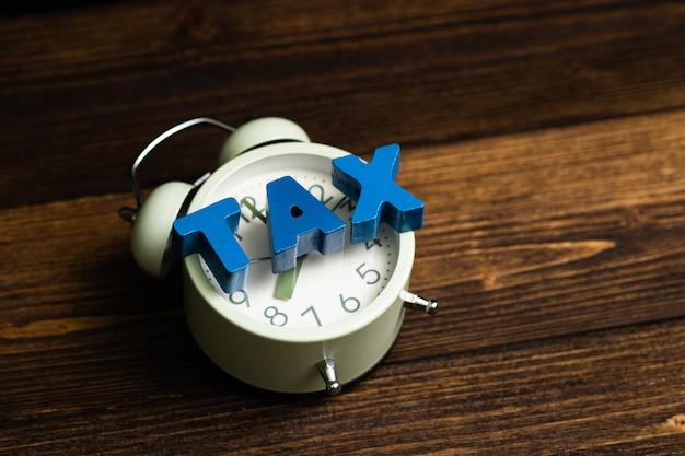 Tributo fiscal y reloj despertador vintage sobre madera.