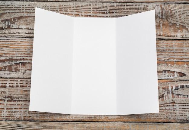 Trifold papel blanco de la plantilla en la textura de madera.