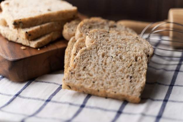 Trigo integral, pan de granos enteros en el tablero de madera oscuro, de cerca, vista desde arriba