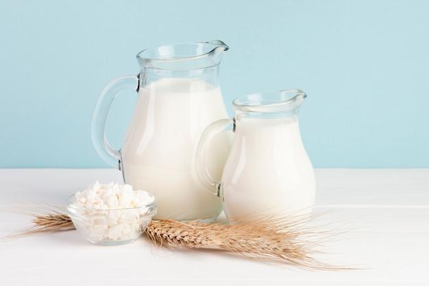 Trigo y jarras con leche fresca.