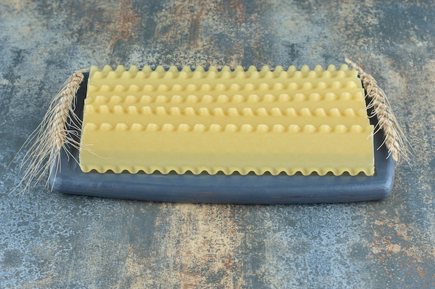 Trigo con láminas de lasaña en el tablero, sobre el fondo de mármol.