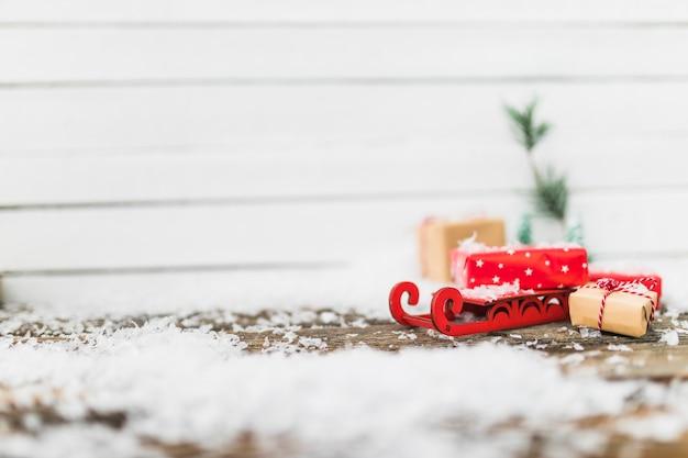 Trineo de juguete cerca de cajas de regalo entre copos de nieve