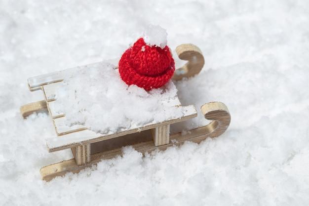 Trineo de madera de estilo retro con gorro de navidad rojo sobre fondo nevado. juguetes de navidad, concepto de celebración de invierno.