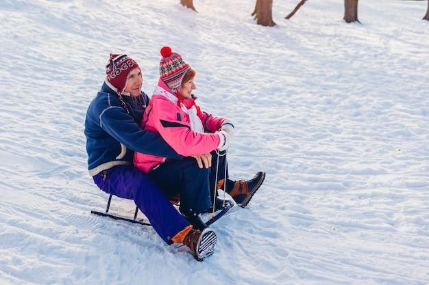 Trineo. senior pareja en trineo hacia abajo. familia divirtiéndose en el parque de invierno. día de san valentín. actividades de invierno