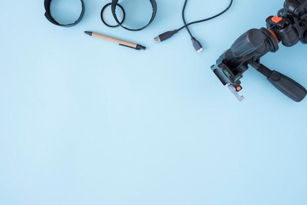 Trípode moderno anillos de extensión con cable y lápiz sobre fondo azul.