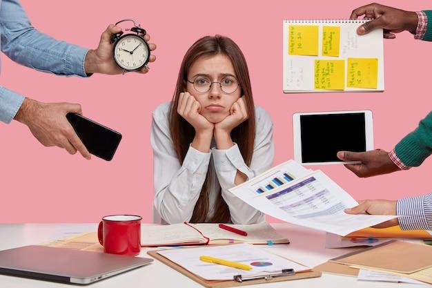 Triste adicta al trabajo mantiene las manos debajo de la barbilla, ocupada haciendo el trabajo del proyecto, estudia papeles, viste una elegante camisa blanca, se sienta en el escritorio, personas desconocidas estiran las manos con notas, reloj despertador, teléfono inteligente