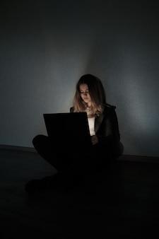 Triste adolescente sentado cerca de la computadora portátil en una habitación oscura. es víctima de acoso en las redes sociales de stalker.