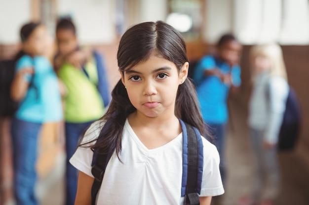 Triste alumno siendo intimidado por compañeros de clase en el pasillo