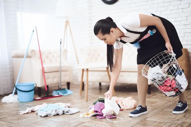 Triste ama de llaves thai maid limpieza desordenada habitación