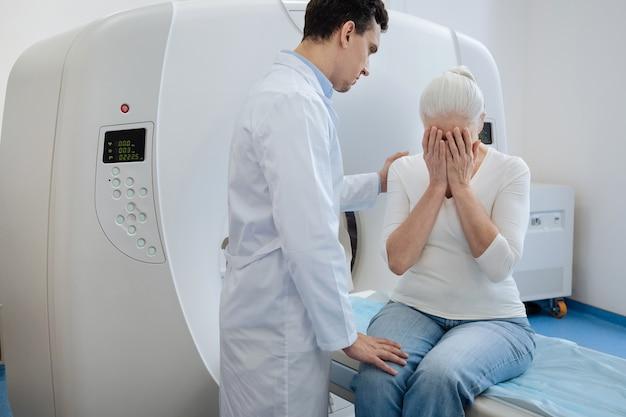 Triste anciana deprimida sentada en la mesa de examen del escáner ct y cubriéndose la cara mientras llora
