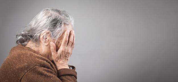 Triste anciana que cubre su rostro.