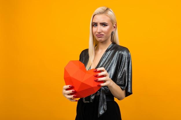 Triste angustiada joven europea sosteniendo un corazón rojo en sus manos sobre una superficie de estudio naranja
