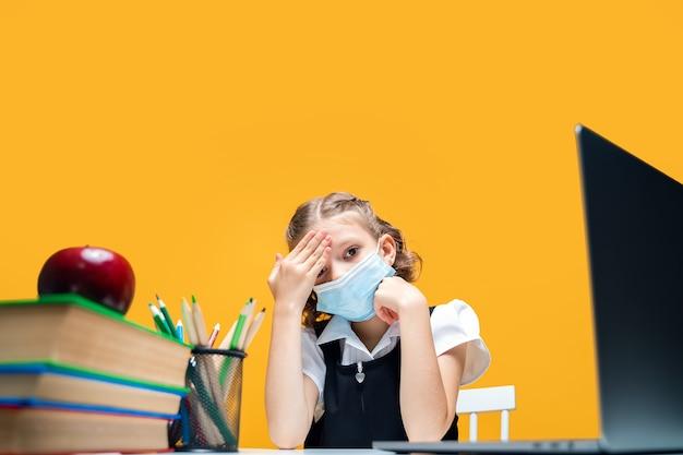 Triste colegiala en una máscara protectora está enferma y sostiene su cabeza con su mano aprendizaje a distancia