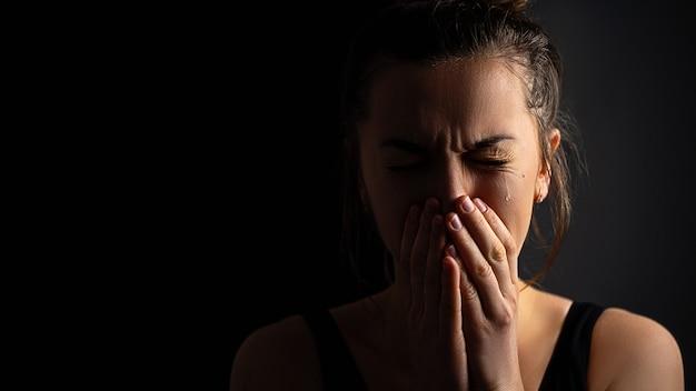 Triste desesperada mujer llorando llorando con las manos juntas y los ojos llorosos