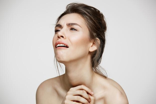 Triste disgustado joven con maquillaje natural sobre fondo blanco. tratamiento facial.