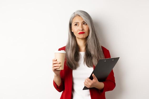Triste empresaria asiática tomando café en el trabajo y mirando la esquina superior izquierda, de pie sobre fondo blanco.