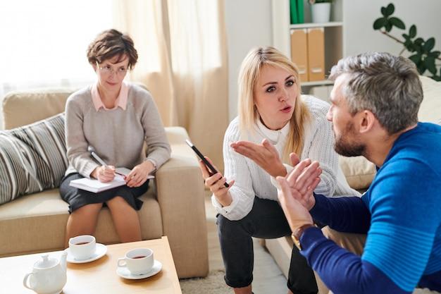 Triste esposa peleando con marido infiel en sesión de terapia