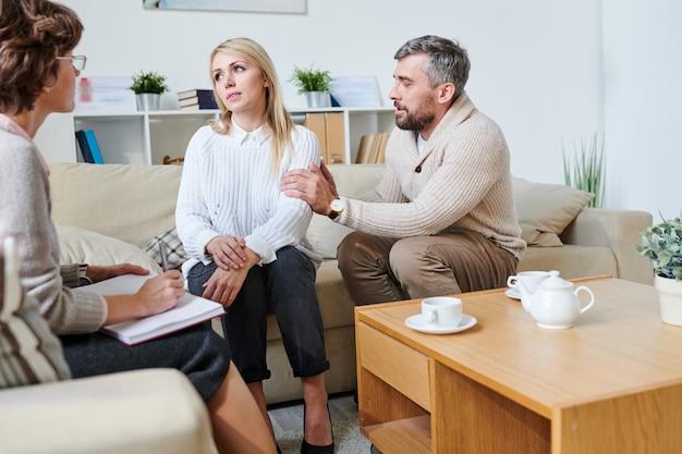 Triste esposo disculpándose con su esposa en la sesión de terapia
