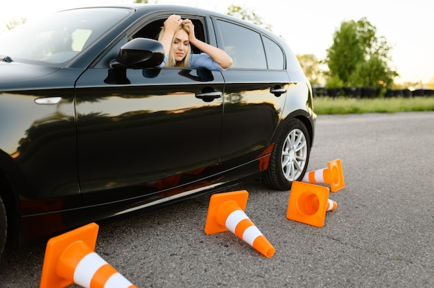 Triste estudiante en coche, todos los conos de tráfico están caídos, lección de autoescuela.