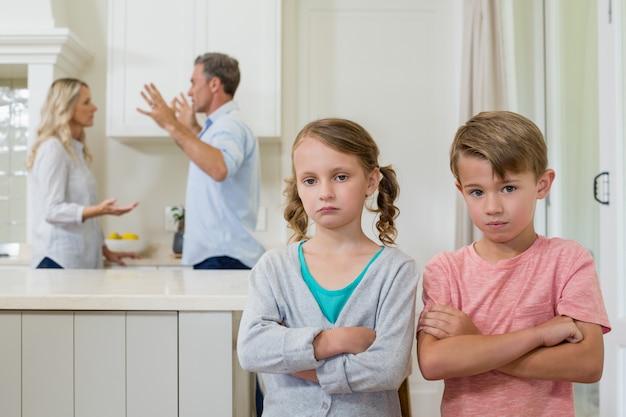Triste hermano de pie con los brazos cruzados mientras los padres se pelean