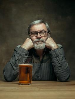 Triste hombre barbudo bebiendo cerveza en pub