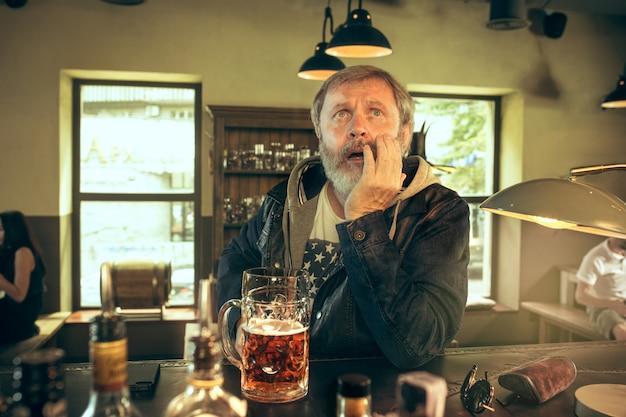 El triste hombre barbudo senior bebiendo cerveza en pub