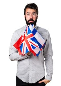 Triste hombre guapo con barba sosteniendo muchas banderas
