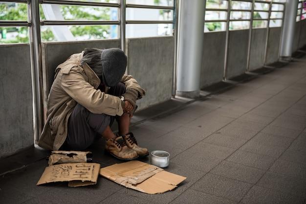 Triste hombre sin hogar en la ciudad
