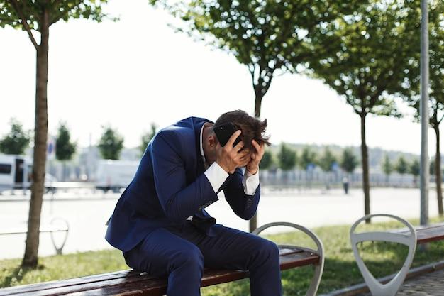 Triste hombre de negocios se sienta en el banco fuera de la calle