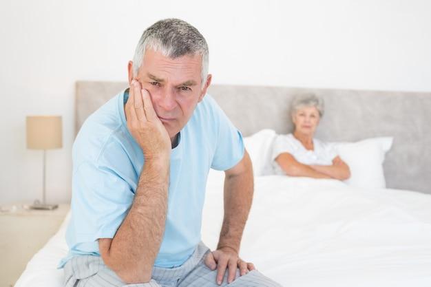 Triste hombre senior con mujer en la cama
