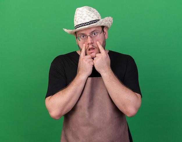 Triste jardinero joven vistiendo sombrero de jardinería tirando hacia abajo los párpados aislados en la pared verde