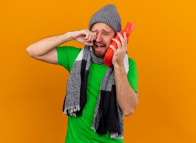 Triste joven apuesto enfermo eslavo con sombrero de invierno y bufanda sosteniendo una bolsa de agua caliente tocando la cara con ella secándose las lágrimas aisladas sobre fondo naranja con espacio de copia